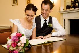 bride and groom sitting at a desk siging of the registry