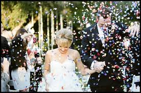 Bride and groom walking down aisle with colourful confetti recessional