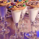 Tall glass of milk with rainbow cookies ontop for children