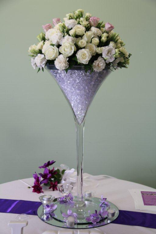 Centerpiece of white and pink flowers in tall glass for a wedding