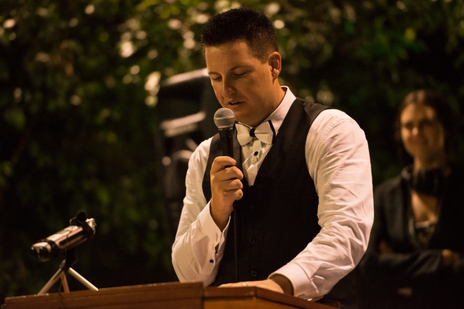 Groom with jacket off holding a microphone giving a speech