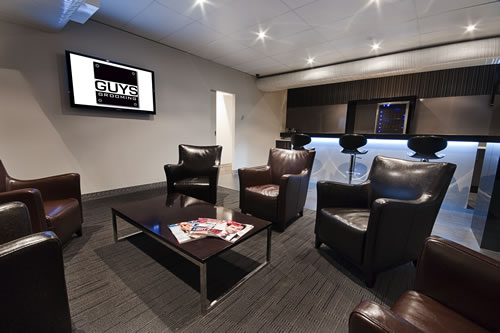 Waiting area of guys grooming with 4 leather chairs, tv and a bar in the background