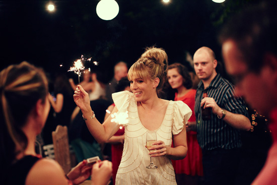 Bride at engagament in white holding sparkler with guests around her