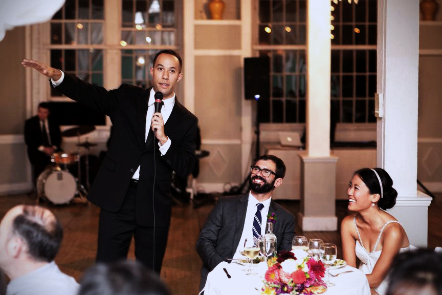 Man mcing a wedding with bride and groom sitting down smiling