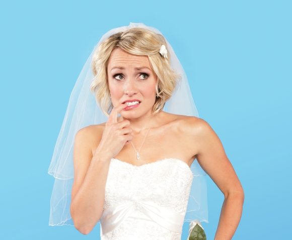 Blue background with bride in white looking concerned and scared