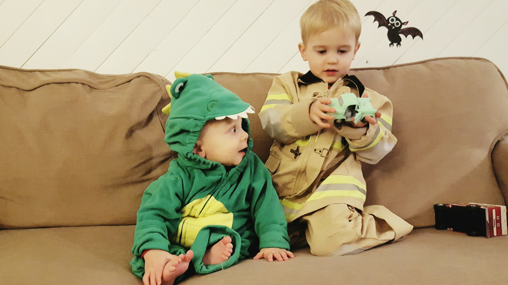 brothers in their costumes. one baby dinosaur and one little fireman. getting my littles to sit still for a photo is impossible!