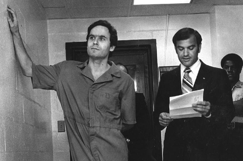 Ted Bundy in a prison jumpsuit leaning with one arm against a wall as a man reads from a piece of paper.