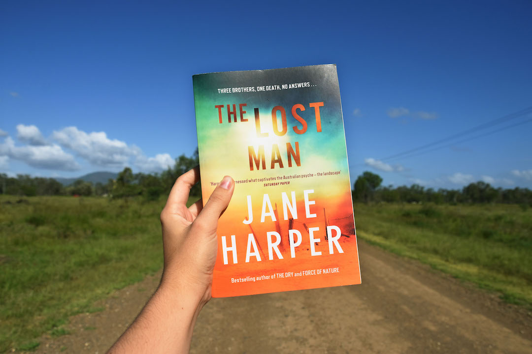 A hand holding The Lost Man by Jane Harper. In the background a dirt road bordered by green bush and blue sky.