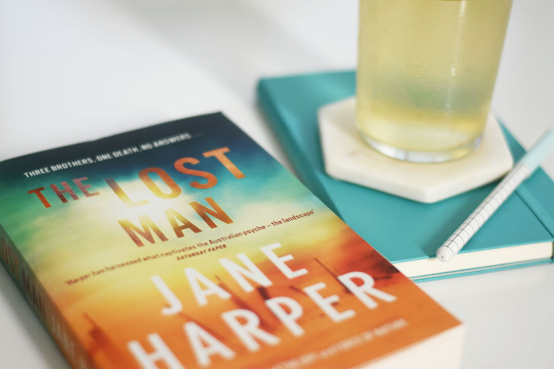 A copy of The Lost Man is prominent in the frame on a white background. To the right, a blue notebook and pen sits underneath a glass of iced tea sitting on a coaster.