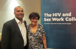 Indoor photo of Pradeep Kakkatil (UNAIDS) and Tracey Tully (APNSW) against backdrop of large banner of the report cover