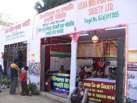"Festival stalls with English and Hindi text including ""USHA Multipurpose Society Ltd"""