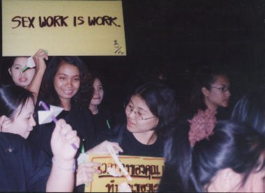 """women holding a placard saying """"Sex Work is Work"""" in English, and partially visible one in Thai language"""