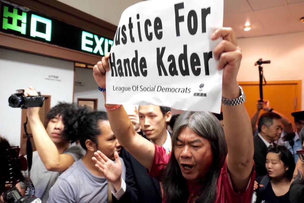 """Indoor photo of a protestor holding a sign which reads """"Justice for Hande Kader"""""""