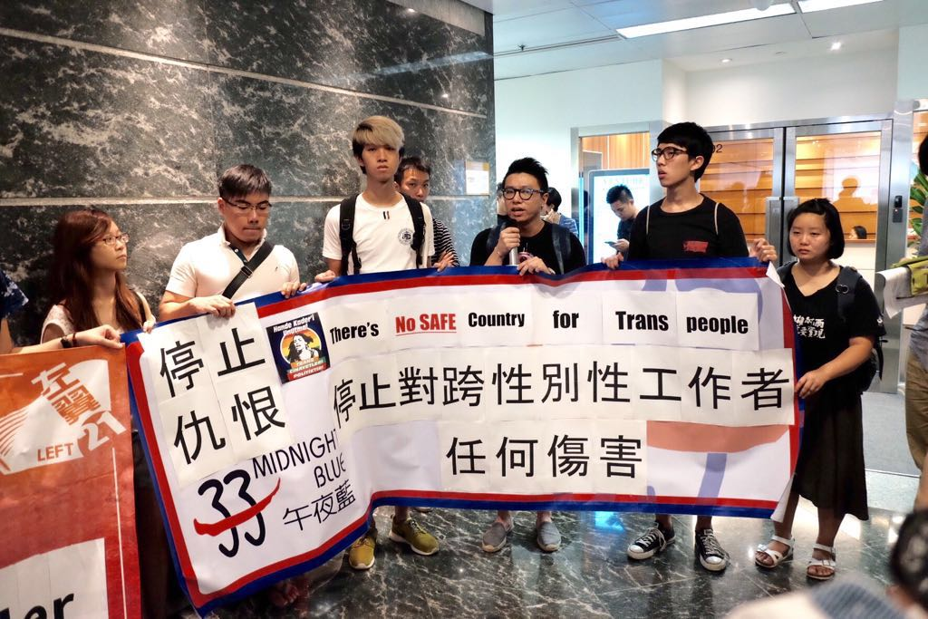"""Indoor photo of protesters holding a long banner in English and Chinese saying """"Justice for Hande Kader"""" and """"There's no safe country for trans people."""""""
