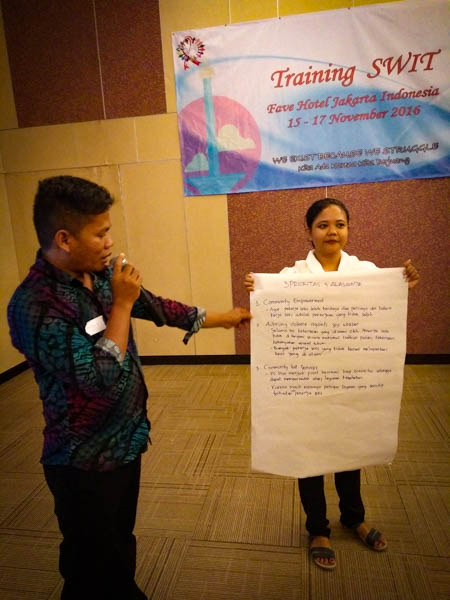 participant holds up flip chart paper with group feedback at SWIT training