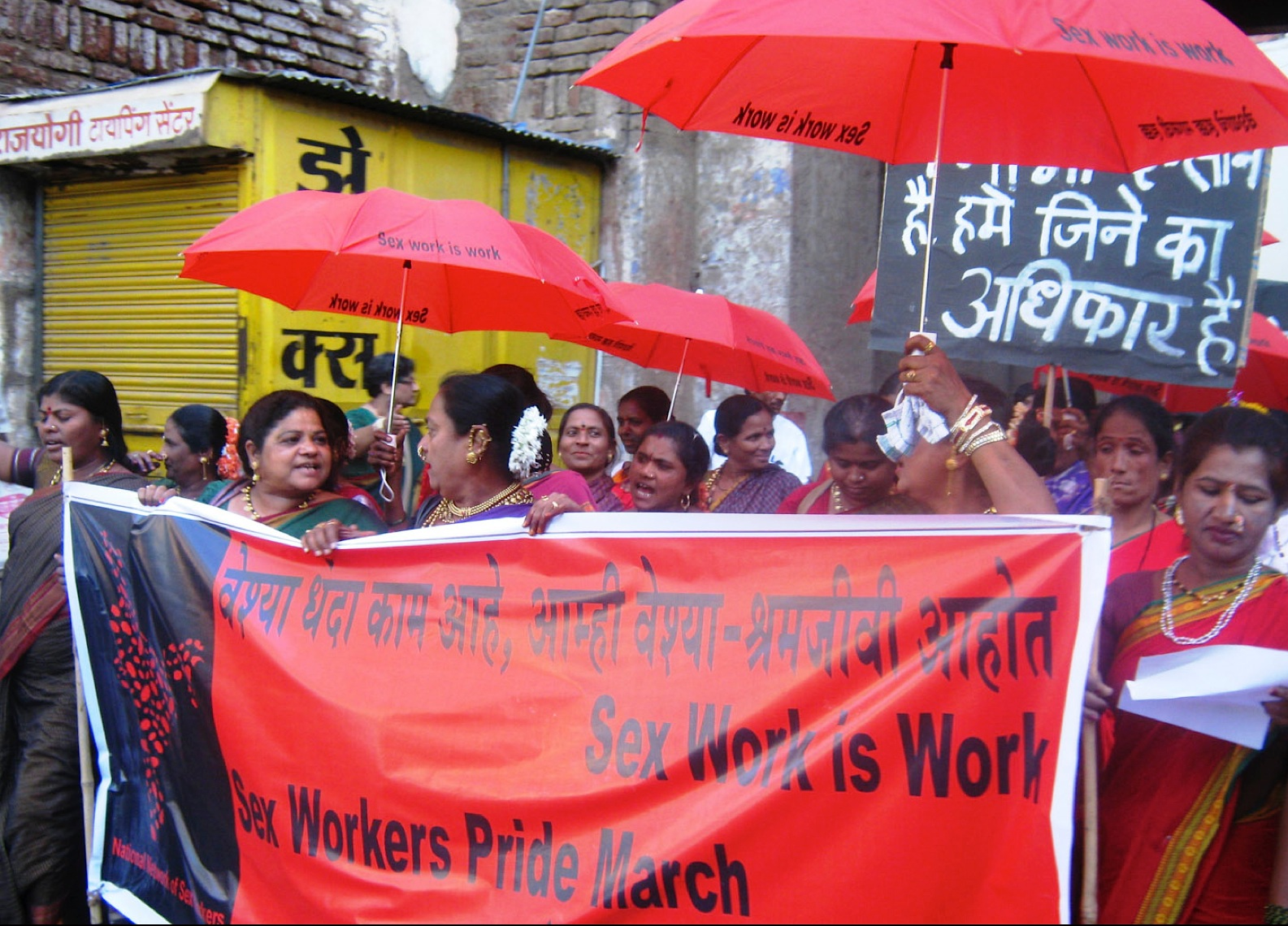 sex workers in India march through the street carrying red umbrellas saying