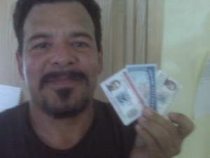 Jose Auraz holds his new Permanent Residence Card, Social Security Card, and Employment Authorization Card.