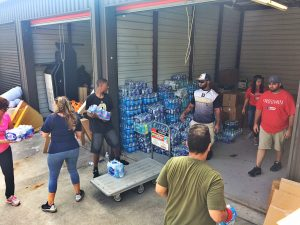 Volunteers form a human chain to unload supplies.