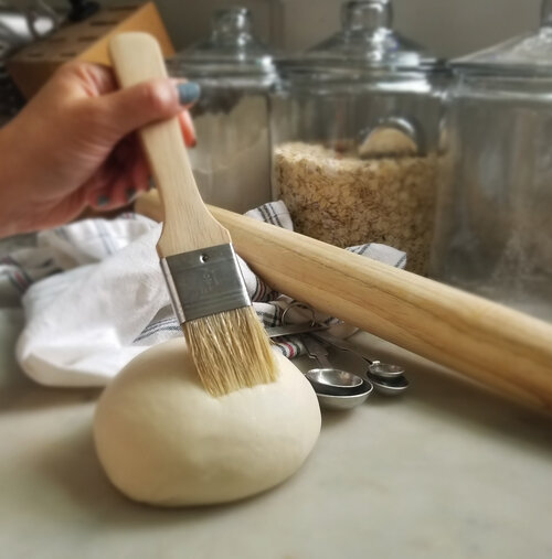 dough being brushed with a pastry brush and baking utensils in the background