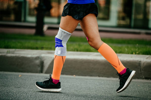 man running on street with knee brace compression sleeve
