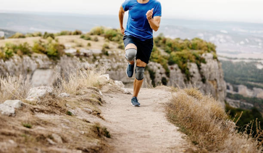 man running on mountain with knee brace compression sleeve
