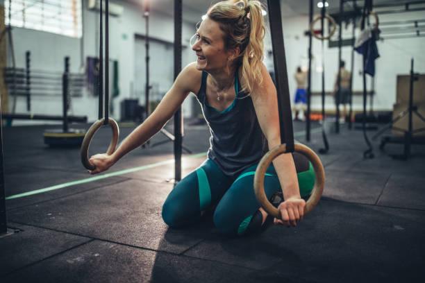 crossfit rings woman in gym workout knee brace