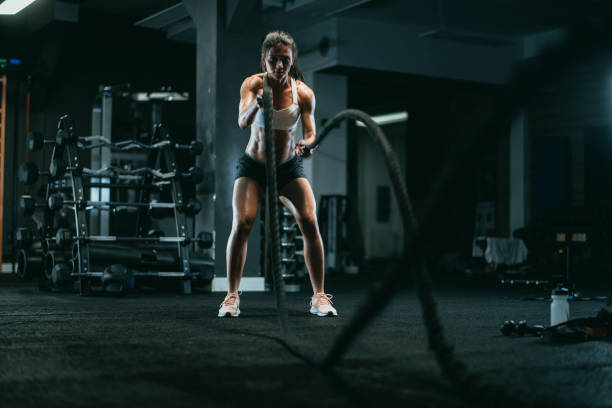 woman with ropes crossfit workout in gym