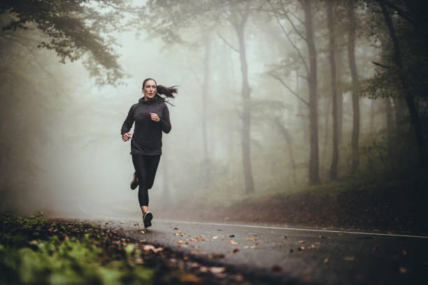 woman running in forest with knee brace