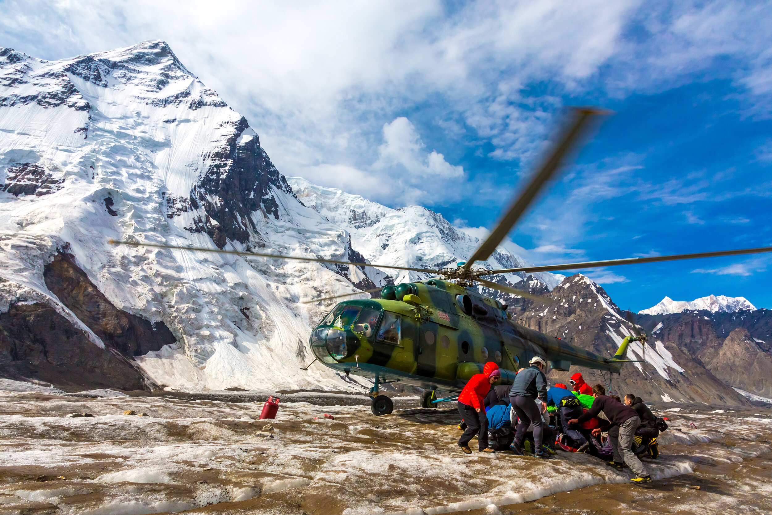 Helicopter Taking Off Ice Field of Massive Glacier and People Holding Luggage