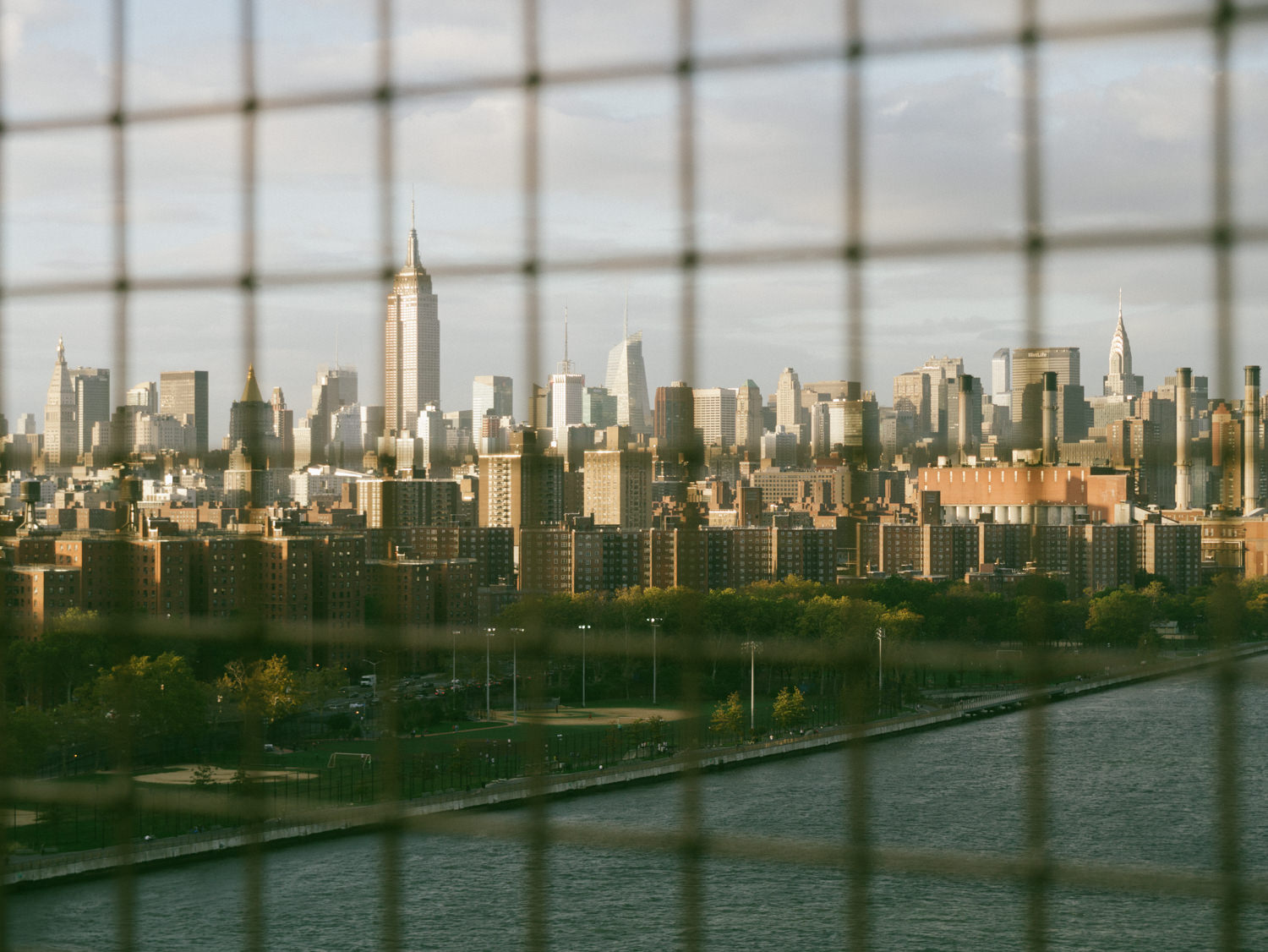 View of the East River Park and Alphabet City in the foreground. Empire State in the background