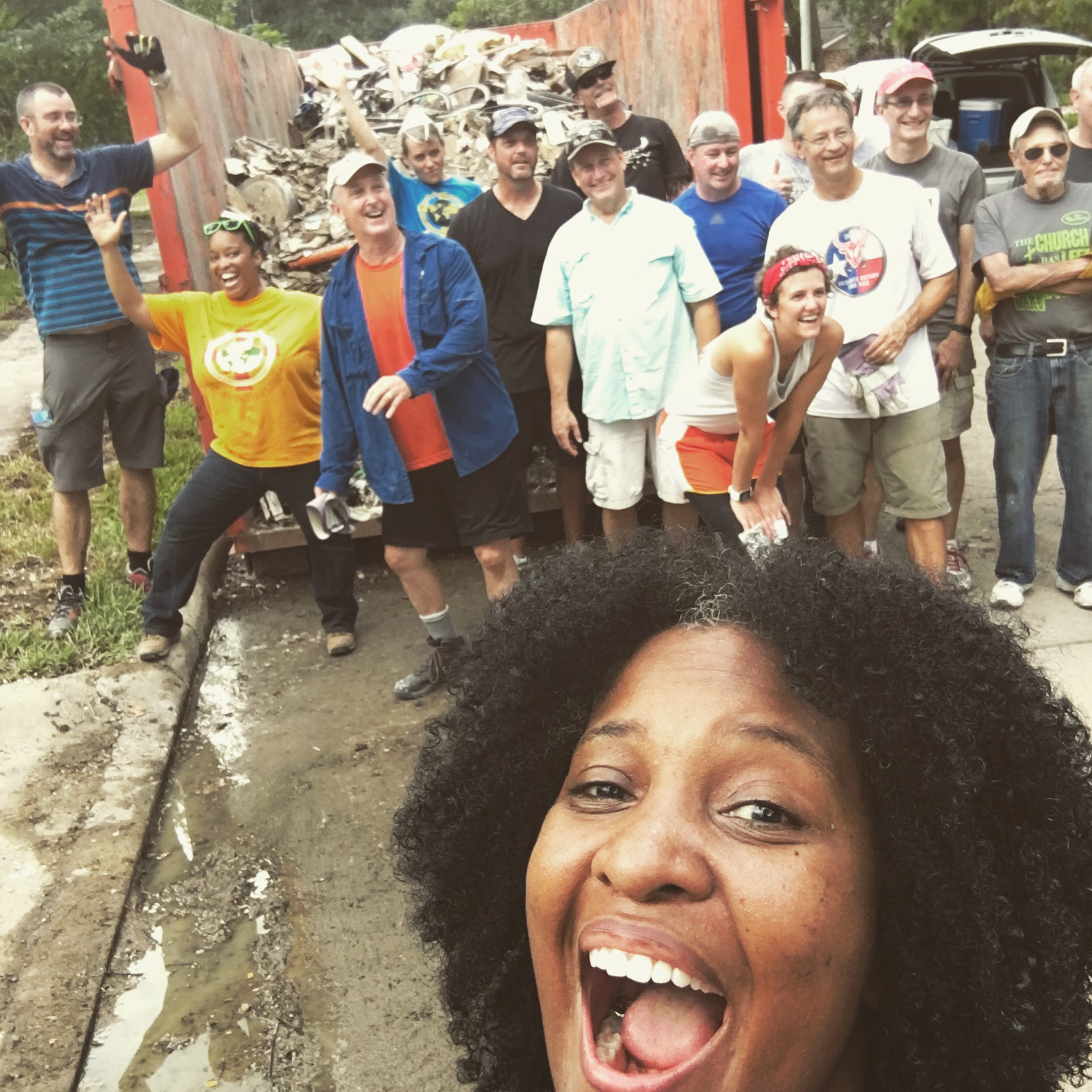 This past weekend,   three volunteer crews from all over Texas miraculously showed up at our house  , taking all that waste you see in the photo at the top of this page, and heaving it into the giant dumpster you see behind us in this photo.  They also helped move all of our salvaged goods into a storage pod.  What would've taken us weeks was accomplished in a matter of hours, because of these fine folks.  Just another one of those mini-miracles that keep popping up.