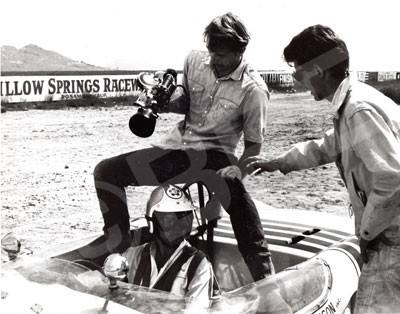 Lucas (right) directing Peter Brock (driver), with camera operator, Emmett Alston (center), mounted on the roll bar for the following shot.