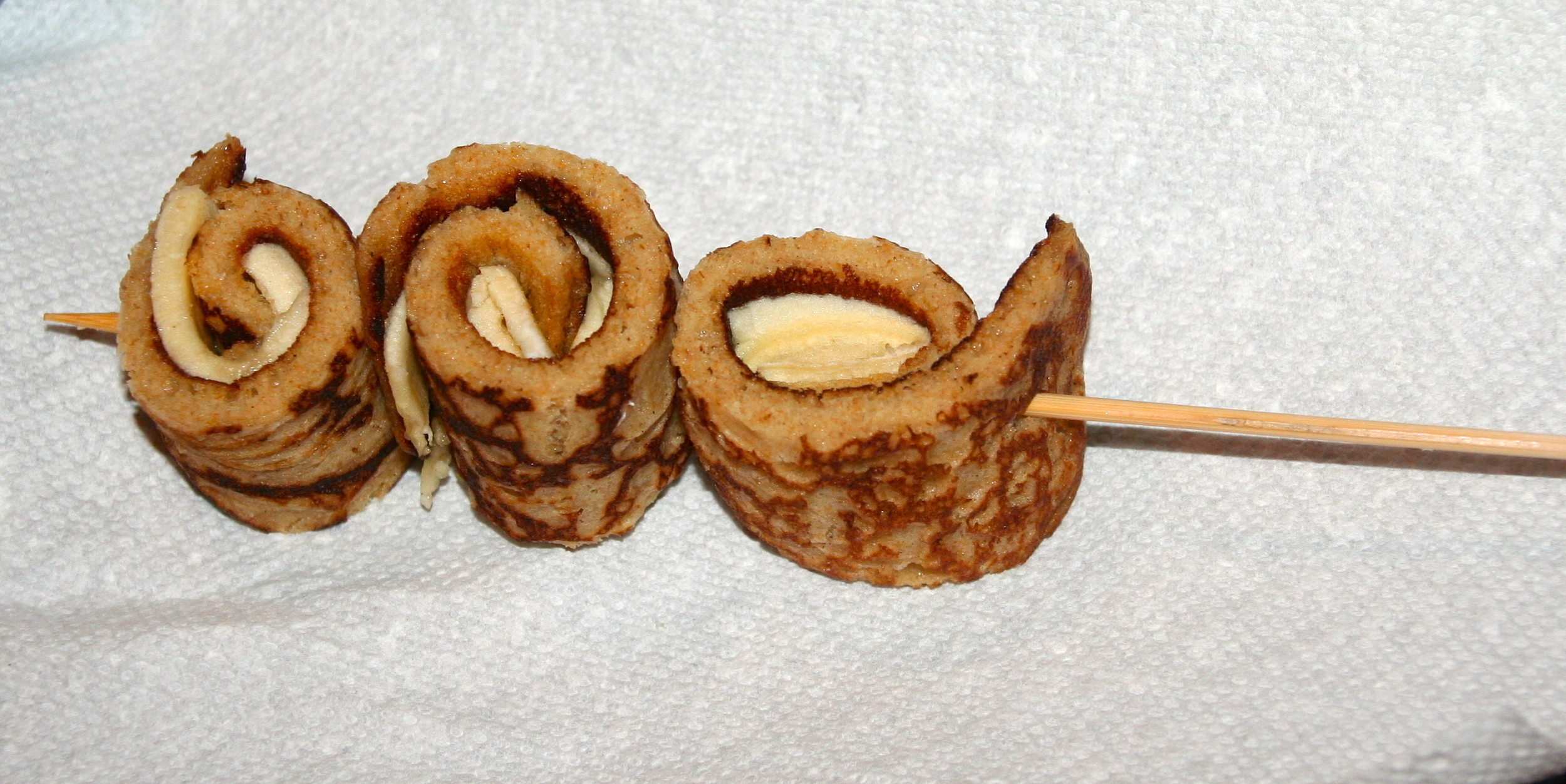 Spear rolled up banana pancakes with kebab stick