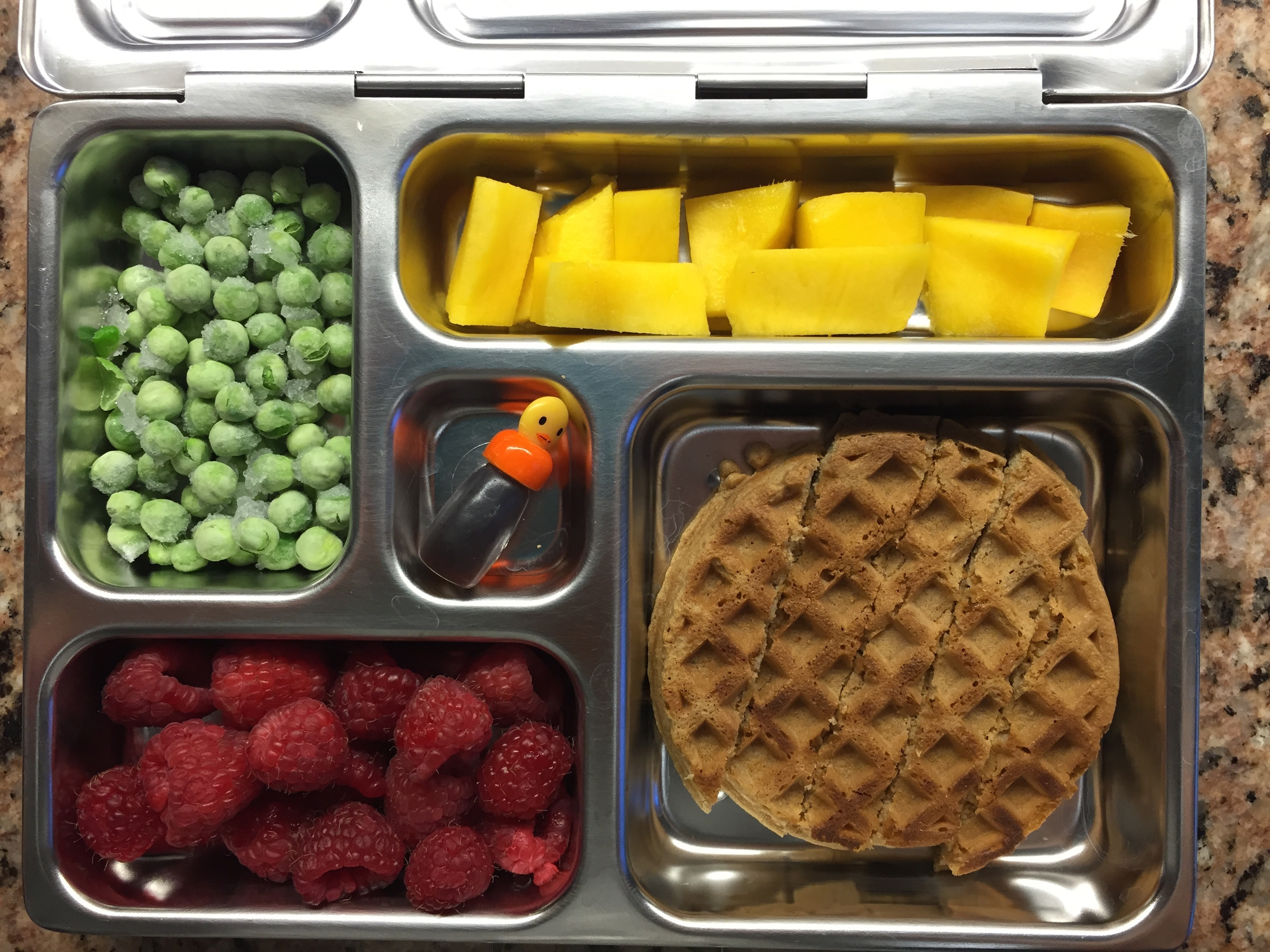 waffle with mini maple syrup, raspberries, frozen peas, mango