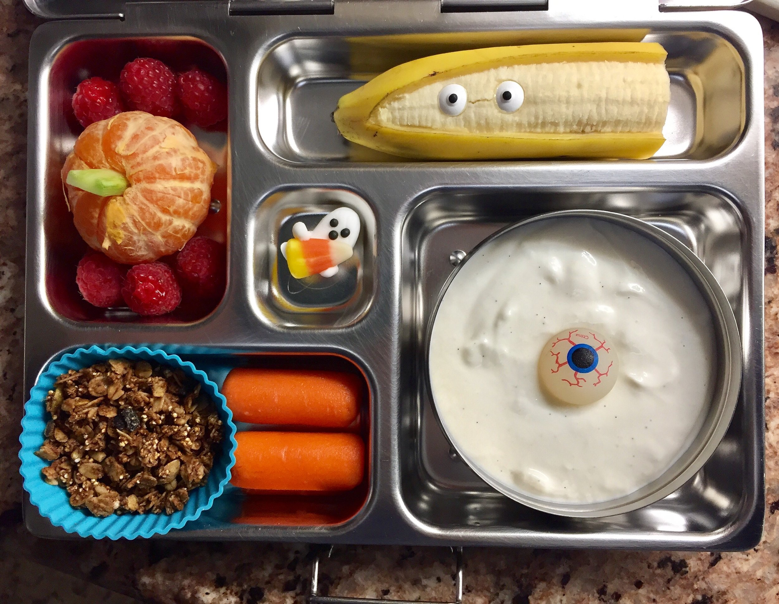 Eyeball yogurt parfait, banana ghost, clementine pumpkin and baby carrots.