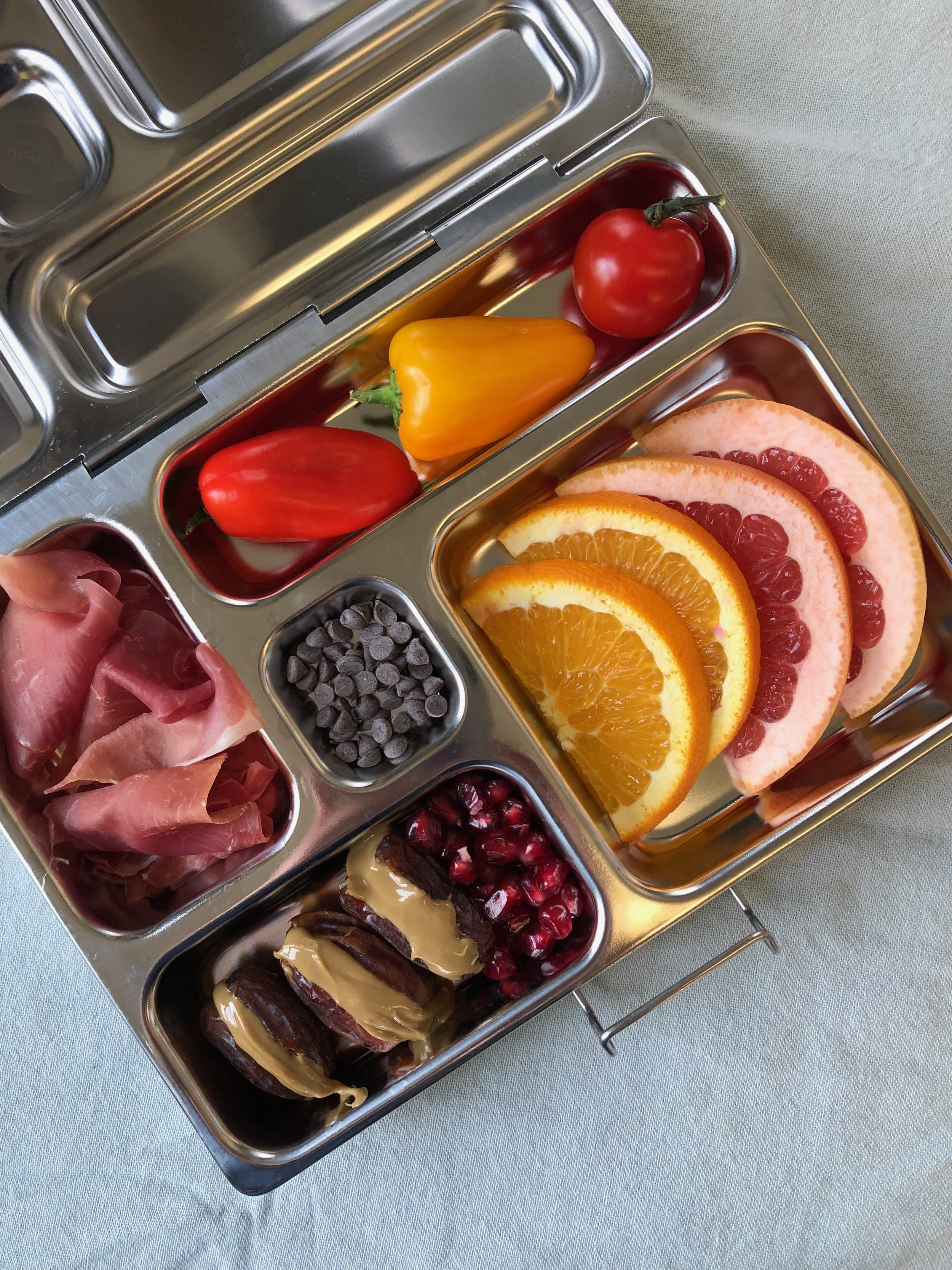 Lunchbox with prosciutto, peppers, grapefruit, pomegranate, dates with sunflower seed butter and chocolate chips.