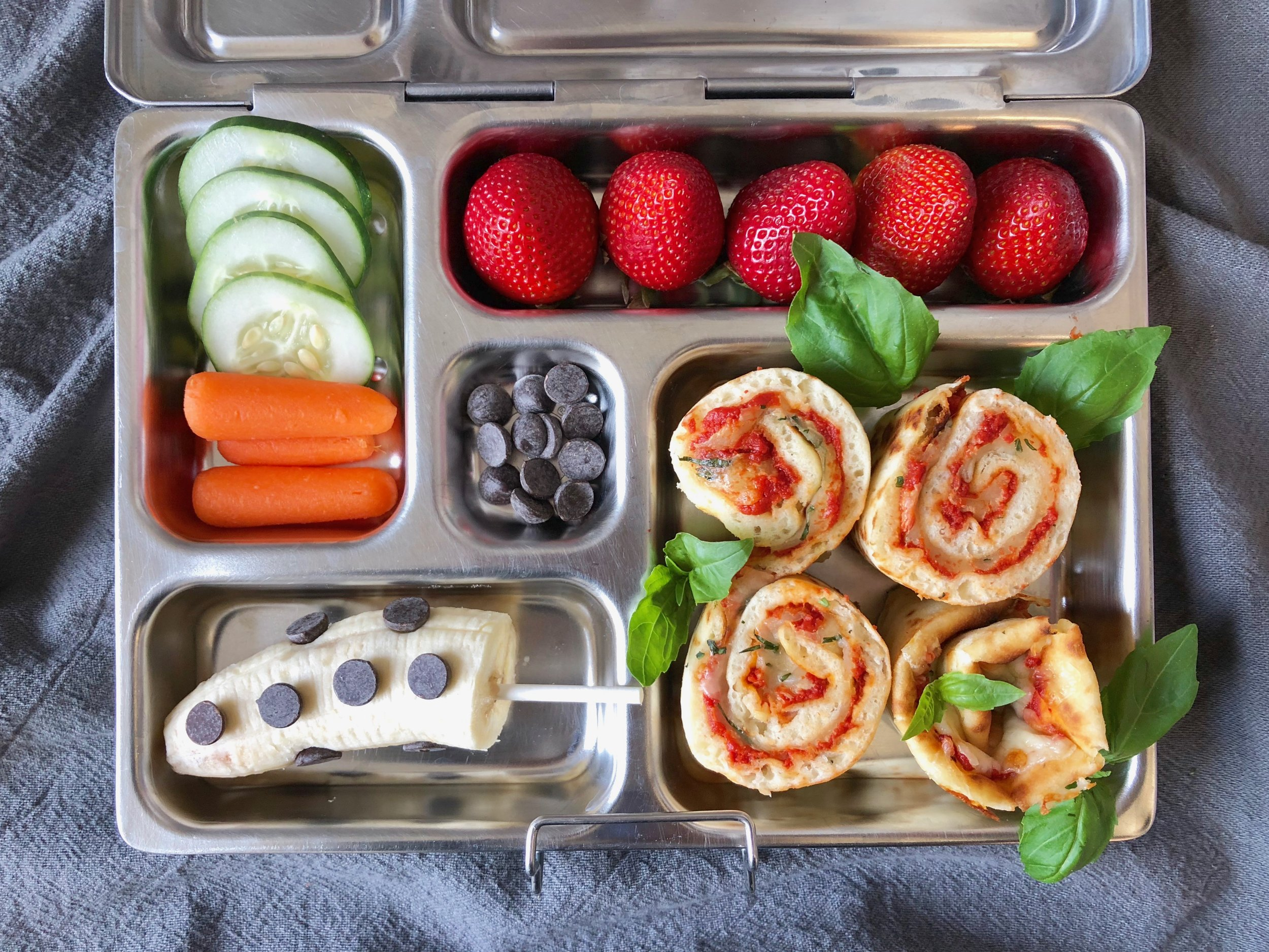 In the lunchbox: pizza rollups, banana with chocolate chips, cucumber and baby carrots, strawberries.