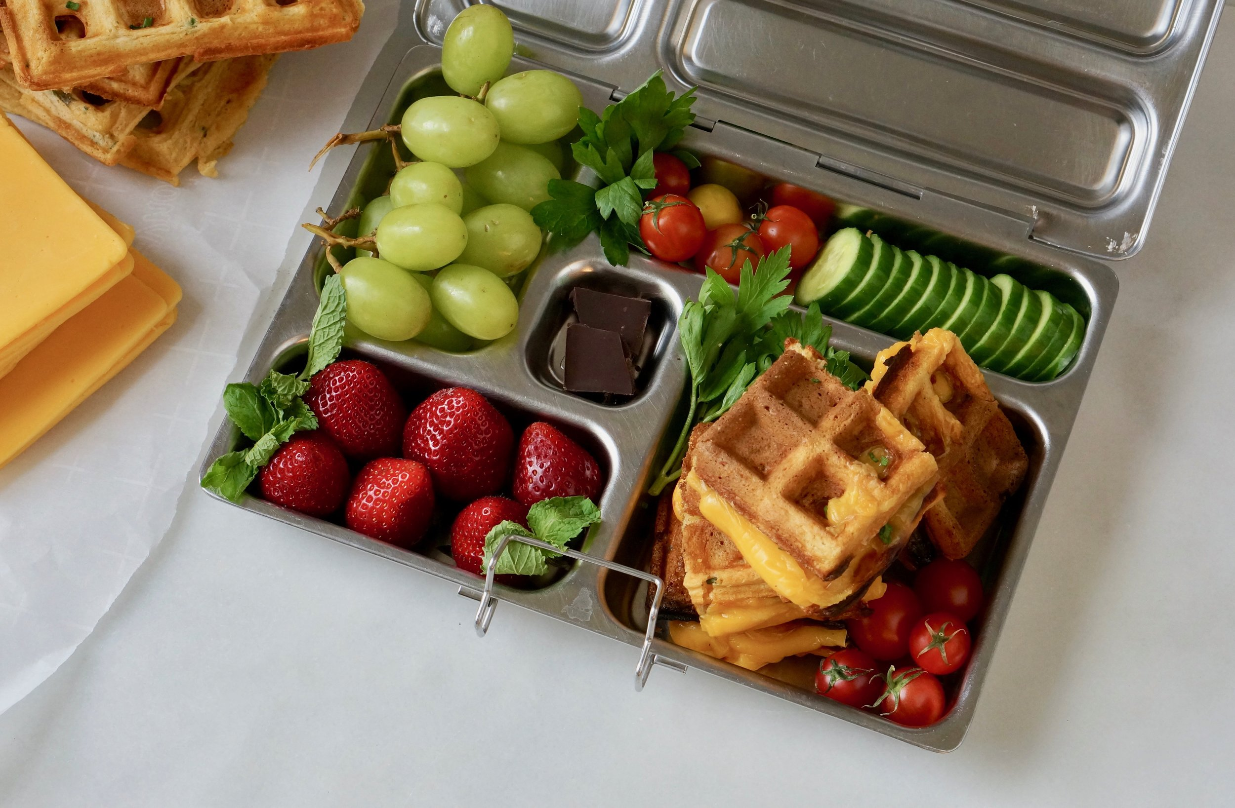 Grilled cheese wafflewich in the lunchbox with strawberries, grapes, tomatoes, cucumber and chocolate.