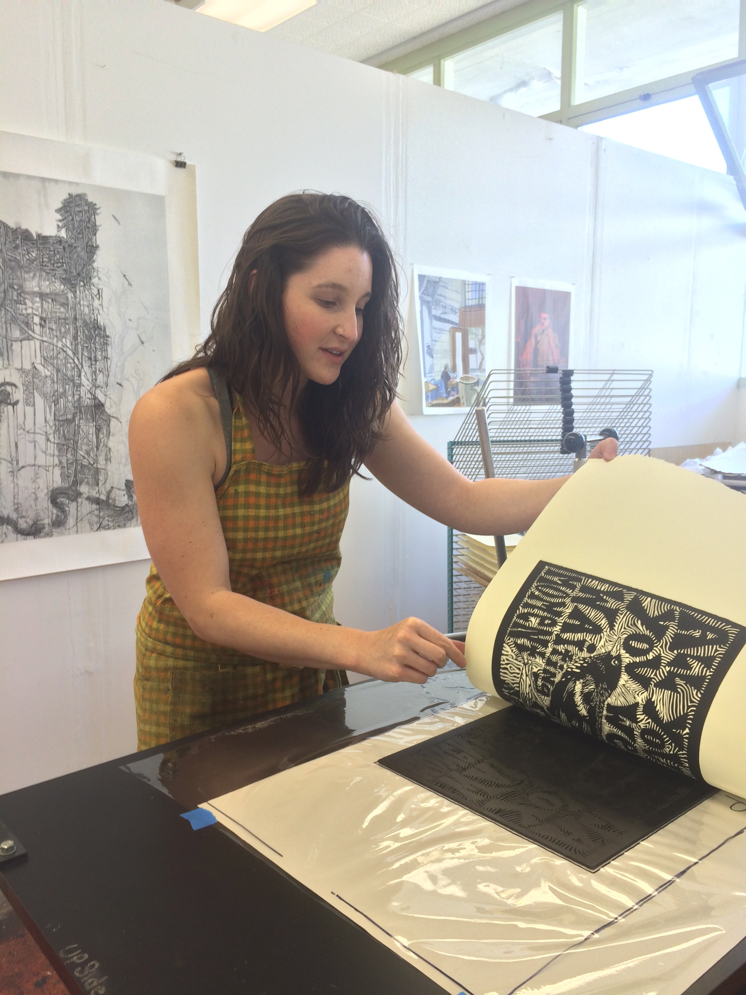 Naomi Branz (Santa Cruz Artist) prints her linoleum block on the etching press.