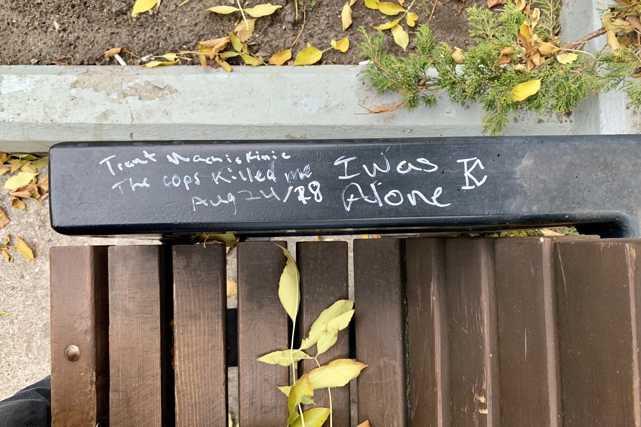 """aerial close-up of the arm on a park bench in Regina's Victoria Park with graffiti that reads """"Trent Machiskinic / The cops killed me / Aug 24/18 / I was Alone"""""""