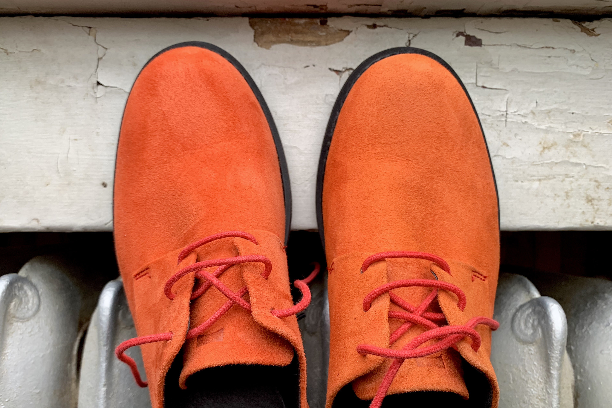 a pair of orange suede campers with red laces