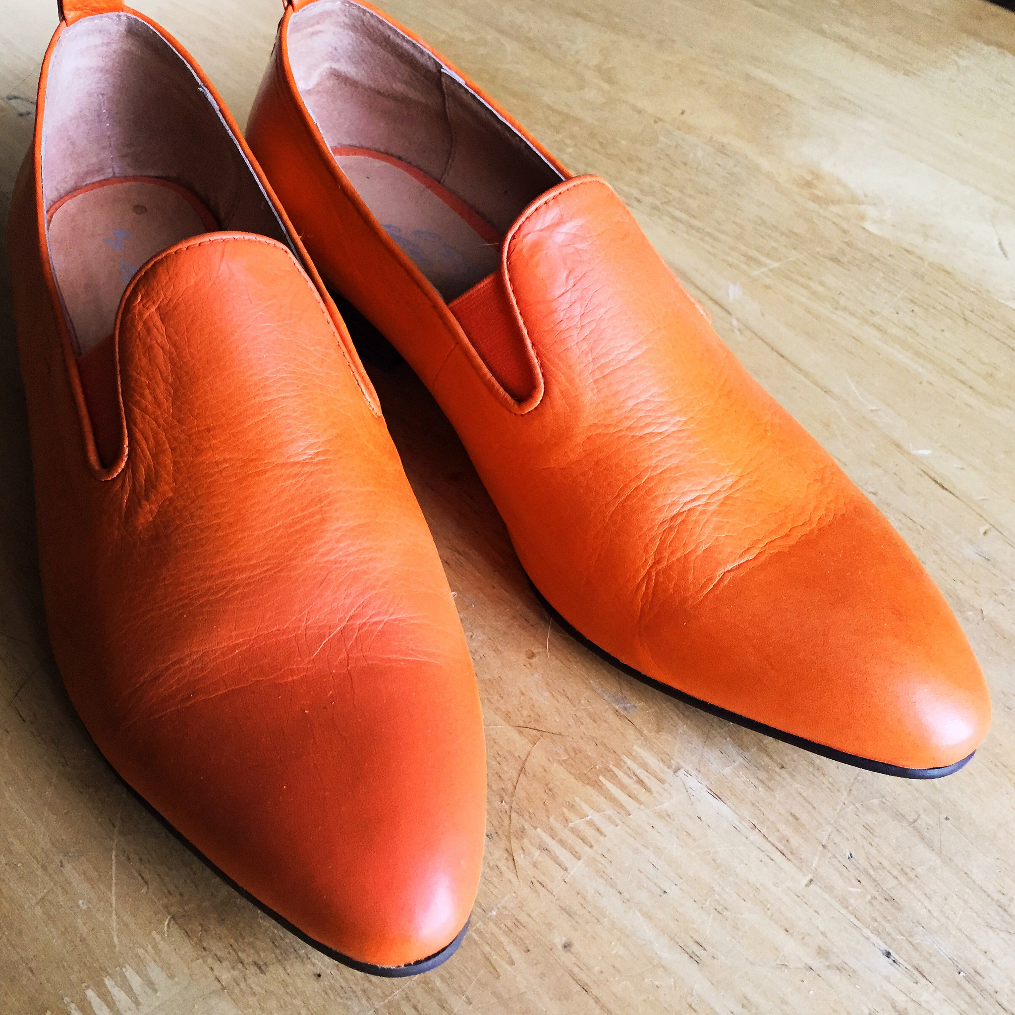 a pair of orange leather ESH by Estée Isman slip-on shoes