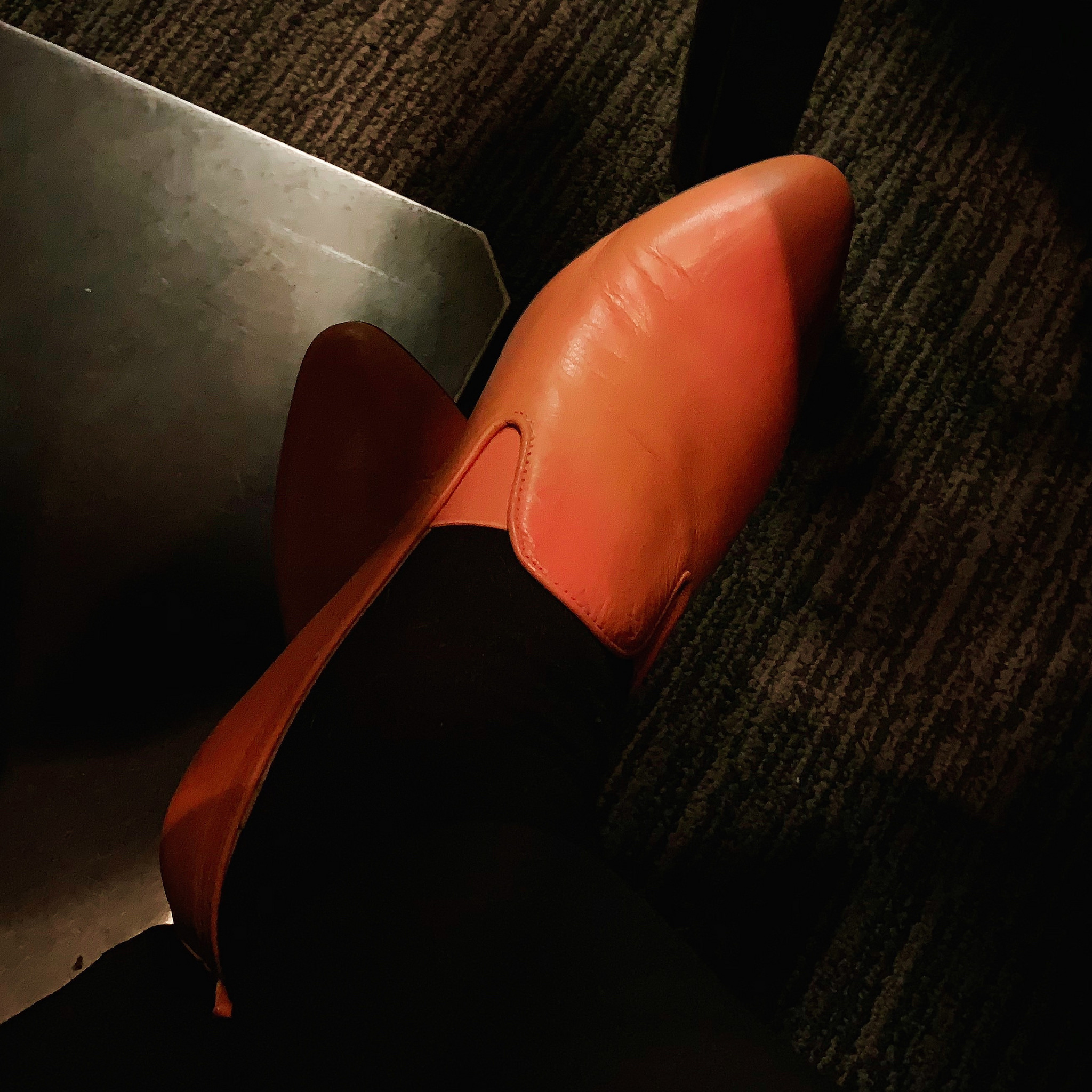 one orange leather ESH by Estée Isman slip-on shoe as seen under a table
