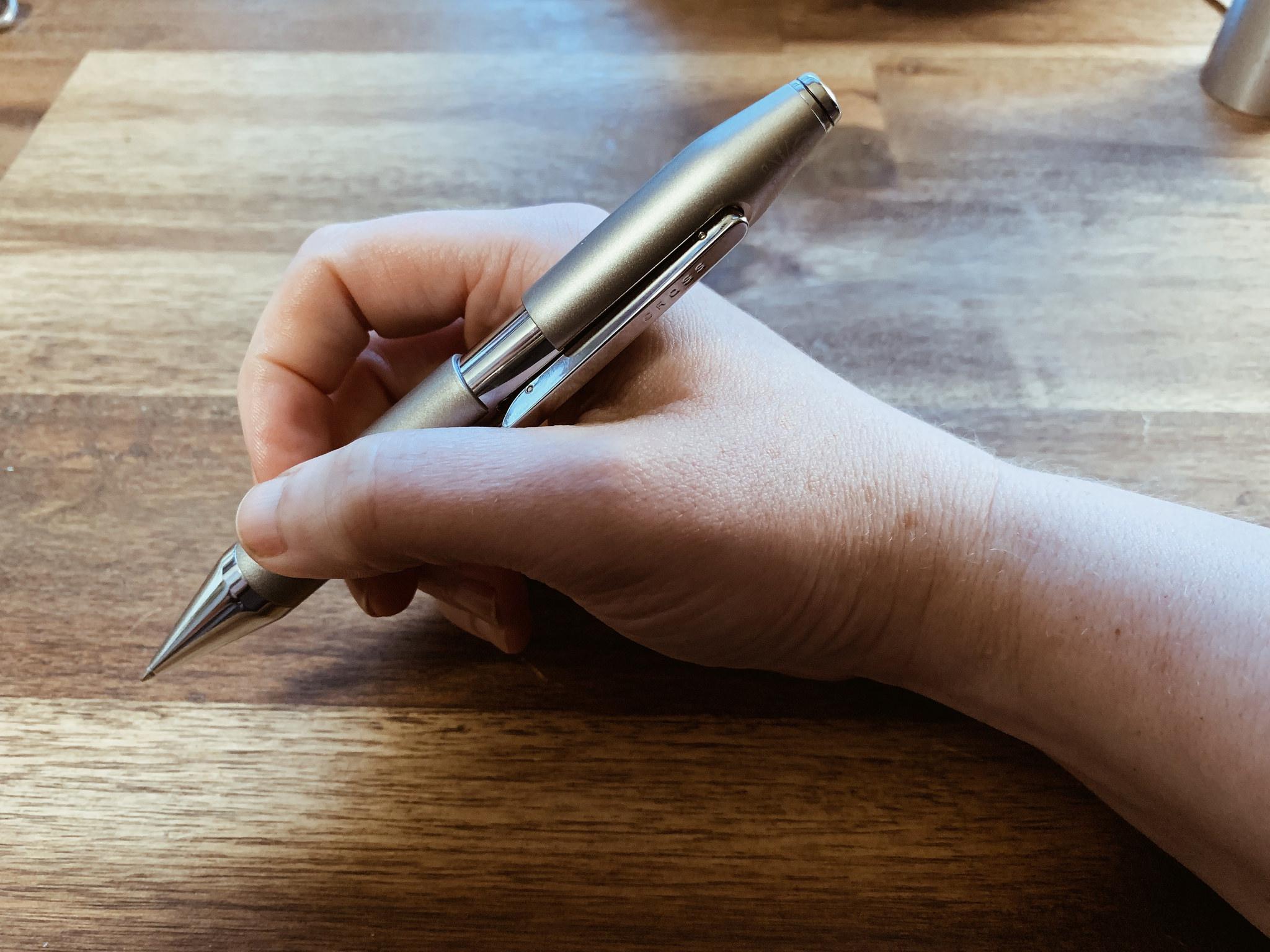 my hand holding my new Cross X graphite grey pen