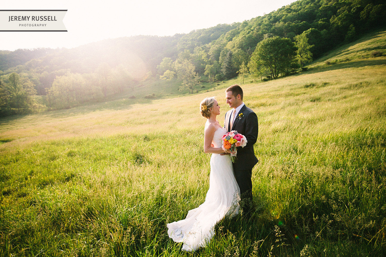 Bride and groom in sunlit field