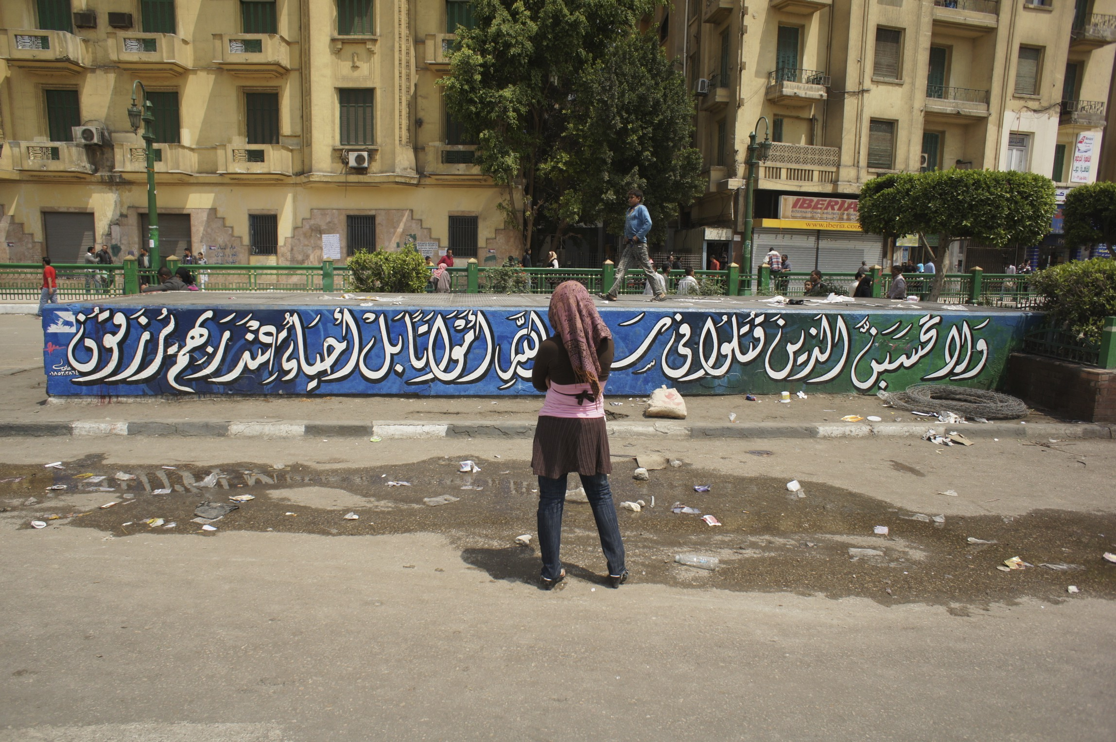A woman looks at a graffiti of a quote from the Quran, Tahrir Square, November 2011. Photo by Issandr El Amrani.
