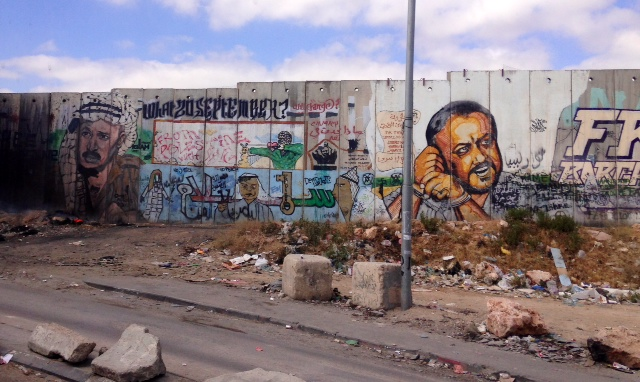 Approaching the Qalandiya Crossing into Jerusalem (the only entrance for Palestinians on foot), graffiti of Yasser Arafat and jailed leader Marwan Barghouti