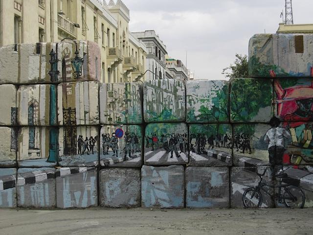 Graffiti on a cinderblock wall blocking an entrance to Tahrir Square