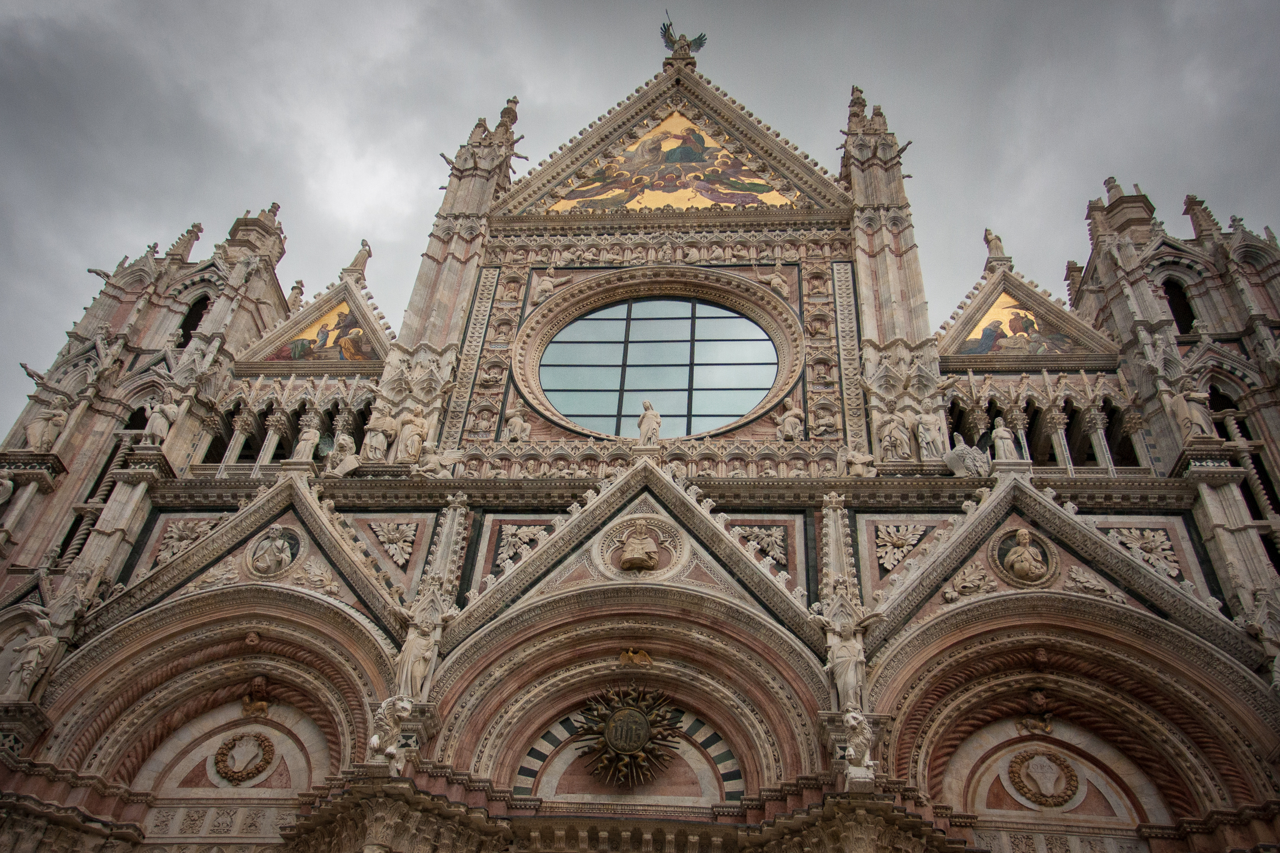 The Facade of the cathedral on an overcast day in Siena.