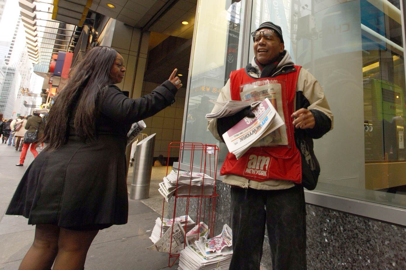 A woman has a friendly interaction with a newspaper man near 5th avenue.